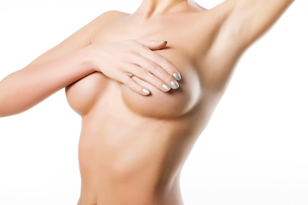 woman covers breasts with her hand