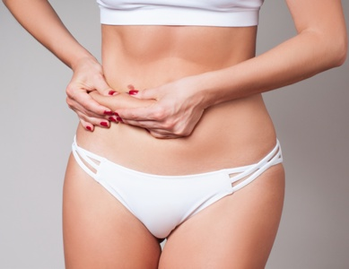 woman with unwanted belly fat considering tummy tuck